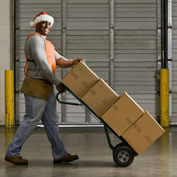 African American warehouse worker pushing boxes on hand truck